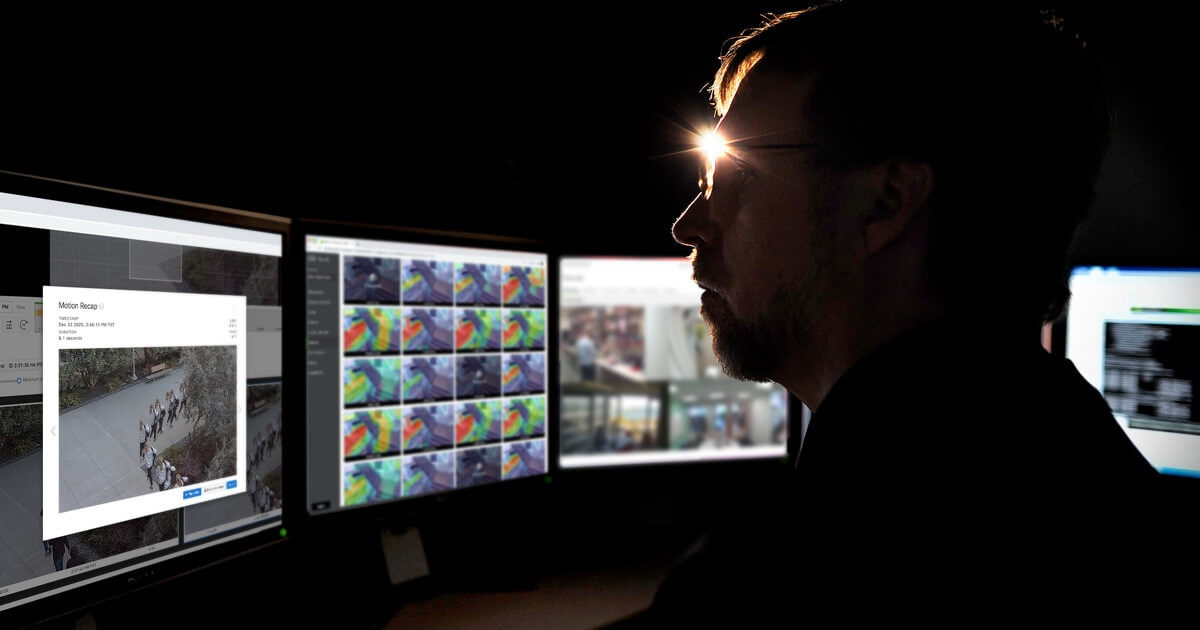 Man viewing security display in a dark room